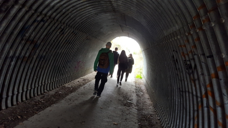 image of young people walking through a tunnel