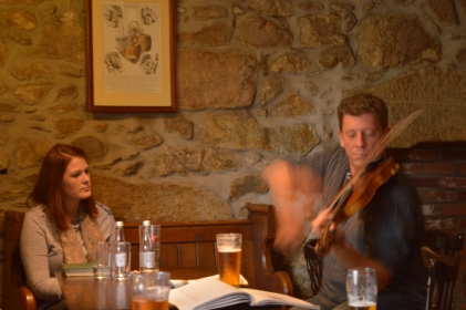 Woman and man sitting at table while man plays fiddle