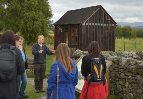 Teacher and students in front of a wooden structure in Newtonmore.