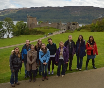 Students and staff standing in front of Urquhart Castle