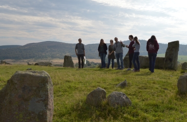 Group standing in front of recumbent stone in stone circle