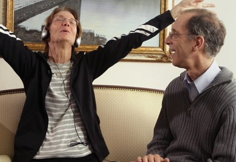 Women wearing headphones raising her arms in the air in joy