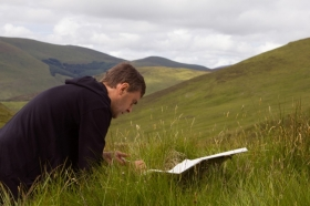 Alec Finlay sitting outside in grass and writing in book. Background of Scottish hills.