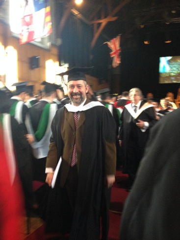 Man in cap and gown walking with diploma in hand