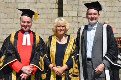 Two men and one woman in graduation ceremony robes
