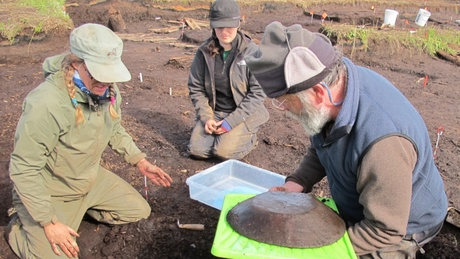 Drs Hillerdal, Forbes and Knecht remove a large wooden bowl from the site