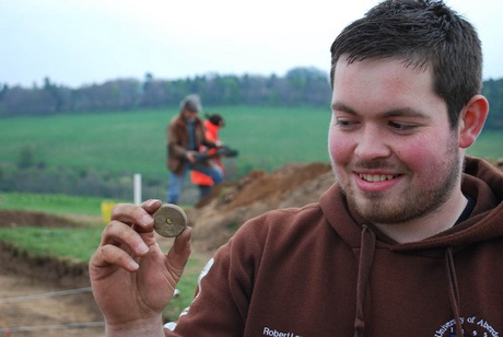 Student Robert Lang with spindle whorl from the possible building site near the Craw Stane at Rhynie