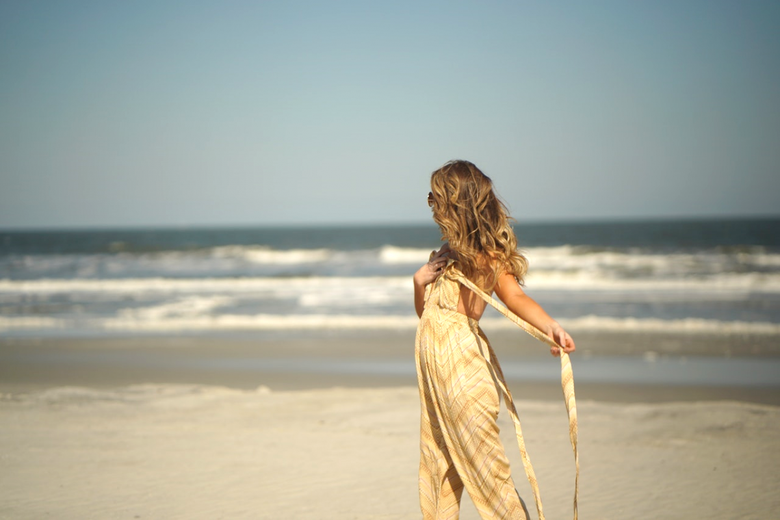 Woman with long hair stands on the beach facing out to sea