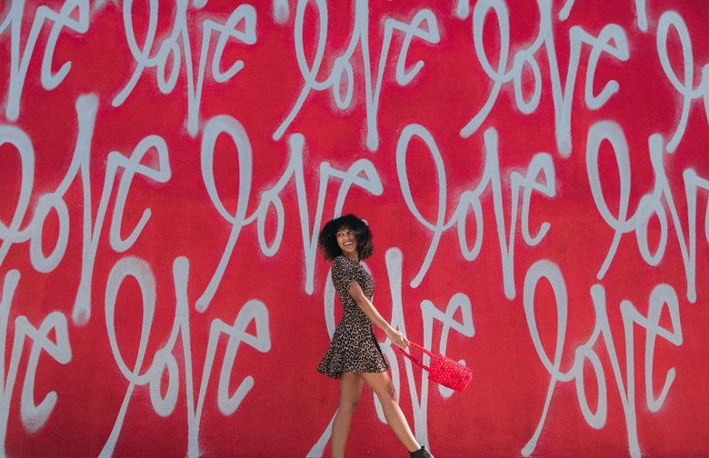 Woman in front of wall with the words Love painted on it