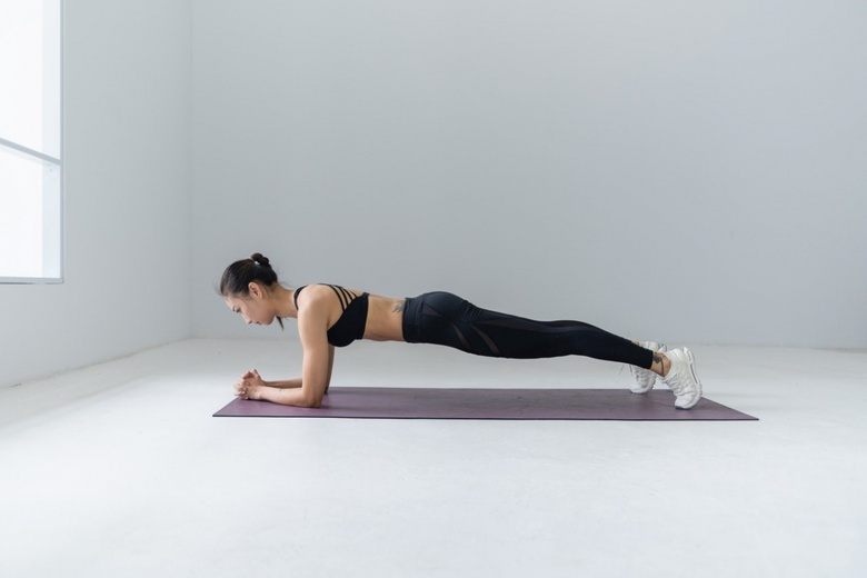 woman does a plank on a yoga mat