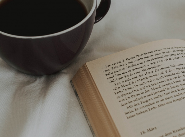 A cup of coffee is shown from bids eye view, positioned next to an open book in warm, calming colours