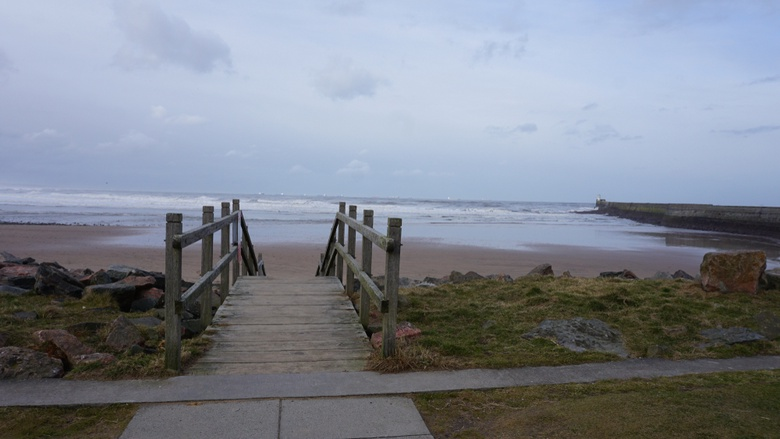 A bridge leading down to Aberdeen beach. the backdrop is a blue sea with a dramatic grey sky.