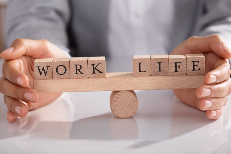 A person balances two groups of blocks, one that spells out work and one that spells out life