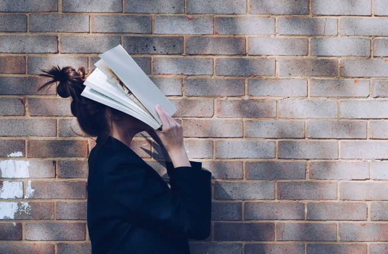 Image of student with head in a book against a brick wall