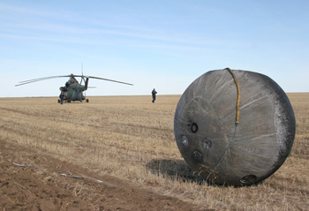 Photo courtesy R. Demets/F. Brandstatter - Spacecraft after landing in Kazakhstan after the experiment. Samples, including Orkney sample, are screwed onto the outside.