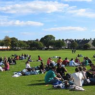 Students sitting on the grass in King's playing field, in the sunshine