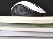 Picture of computer mouse on top of a folders and books