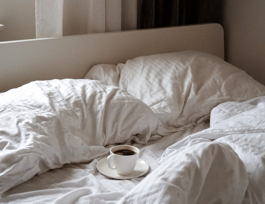 A cup of coffee on a saucer sits in the middle of an unmade bed with crisp white sheets