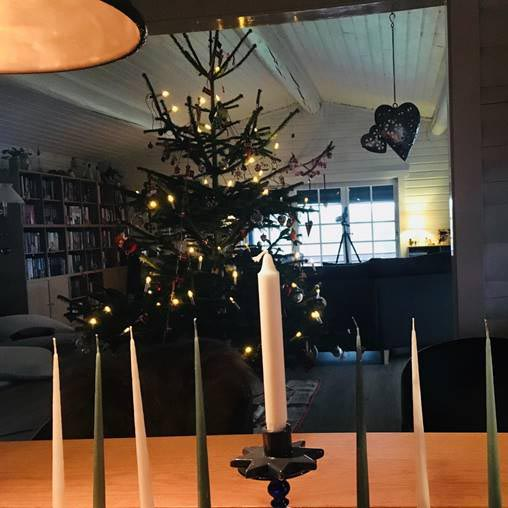 Candles on a table, and a decorated fir tree in the background